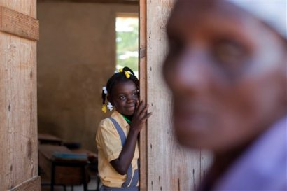 In this Tuesday, March 25, 2014 photo, Brenia Petit-Jean, 12, looks out from a classroom while her mother queues for food donated by the U.N. World Food Program, WFP, at a local school in Bombardopolis, northwestern Haiti. (AP Photo/Dieu Nalio Chery)
