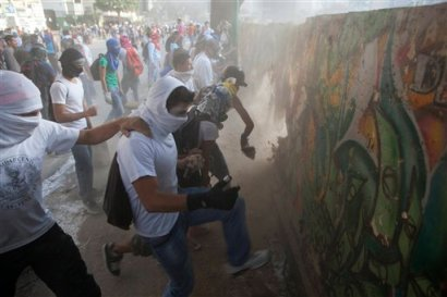 Demonstrators destroy a wall in order to have more rocks to throw at the Bolivarian National Guard during anti-government protests in Caracas, Venezuela, Tuesday, March 4, 2014. A year after the death of Hugo Chavez, Venezuela has been rocked by weeks of violent protests that the government says have left 18 dead. (AP Photo/Rodrigo Abd)