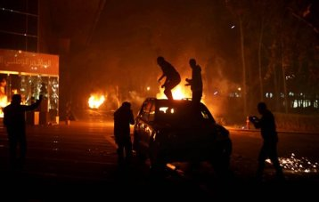 In this Sunday, March 2, 2014 photo, protesters stand atop a vehicle as others burn in front of the National Conference Hall, in Tripoli, Libya. (AP Photo/Mohamed Ben Khalifa)