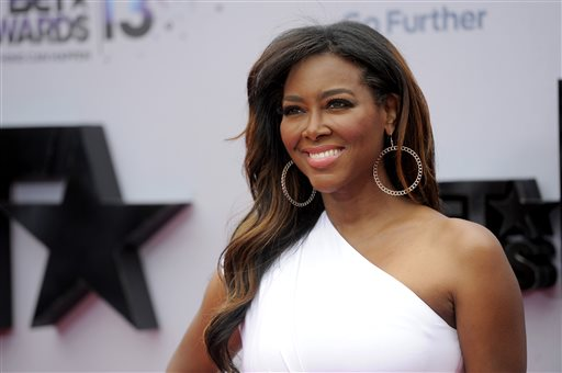 """This June 30, 2013 file photo shows TV personality Kenya Moore at the BET Awards in Los Angeles. Moore says she's seriously considering leaving """"The Real Housewives of Atlanta"""" after her televised brawl with co-star Porsha Williams. Williams surrendered last week to authorities and was charged with a misdemeanor charge of battery for the fight, which was televised as part of the Bravo show's reunion special on Sunday, April 20. (Photo by Chris Pizzello/Invision/AP, File)"""