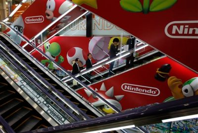 Shoppers take escalators under the logo of Nintendo and Super Mario characters at an electronics store in Tokyo Wednesday, May 7, 2014. Nintendo Co. sank to a loss for the fiscal year ended March as sales of its Wii U game machine continued to lag, but the Japanese manufacturer of Pokemon and Super Mario games promised Wednesday to return to profit this year. (AP Photo/Shizuo Kambayashi)