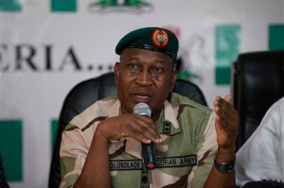 Brig. Gen. Chris Olukolade, Nigeria's top military spokesman, speaks during a press conference on the abducted school girls in Abuja, Nigeria, Monday, May 12, 2014. A Nigerian Islamic extremist leader says nearly 300 abducted schoolgirls will not be seen again until the government frees his detained fighters. A new video from Nigeria's homegrown Boko Haram terrorist network received Monday purports to show some of the girls and young women chanting Quranic verses in Arabic. The barefoot girls look frightened and sad and sit huddled together wearing gray Muslim veils. Some Christians among them say they have converted to Islam. (AP Photo/Sunday Alamba)