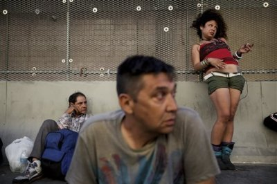 George Mendez, foreground, a 55-year-old recovering alcoholic, sits in front of a drunk woman in the Skid Row area of Los Angeles on Tuesday, July 23, 2013. The area, originally agricultural until the 1870s when railroads first entered Los Angeles, has maintained a transient nature through the years from the influxes of short-term workers, migrants fleeing economic hardship during the Great Depression, military personnel during World War II and the Vietnam conflict, and low-skilled workers with. (AP Photo)