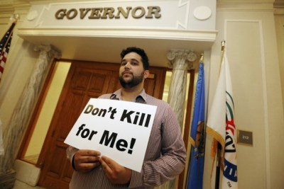Hossein Dabiri with Oklahoma Coalition Against the Death Penalty holds a sign protesting the death penalty at the State Capitol in Oklahoma City on Tuesday. (Steve Gooch/AP)
