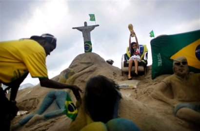 A young girl lifts a replica of the World Cup trophy next to a sand sculpture of Rio de Janeiro's iconic Christ the Redeemer along the Copacabana beach, Wednesday, June 11, 2014 in Rio de Janeiro, Brazil. The World Cup 2014 tournament will be held in Brazil and starts on June 12. (AP Photo/Wong Maye-E)