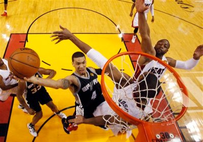 San Antonio Spurs guard Danny Green (4) drives to the basket over Miami Heat center Chris Bosh (1) and  guard Dwyane Wade (3)during the first half in Game 3 of the NBA basketball finals, Tuesday, June 10, 2014, in Miami. (AP Photo/Wilfredo Lee)