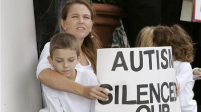 Christine Gianadda, of Dallas, holds a sign and her son, Gordon, 8, who has Asperger syndrome, as they participate in a demonstration outside a hotel in Richardson, Texas. (AP Photo/Tony Gutierrez)