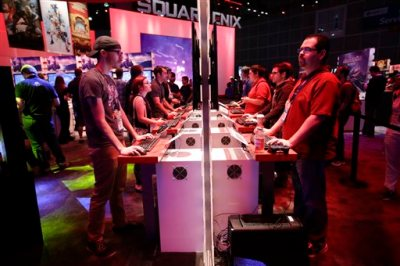 In this Thursday, June 12, 2014 file photo, people play a video game at the Square Enix booth at the Electronic Entertainment Expo, in Los Angeles. At last week's E3, video game developers hyped upcoming titles featuring assassins, super-soldiers, vigilantes and demon hunters. The lack of female protagonists at the expo highlighted an ongoing issue that continues to haunt the video game industry. (AP Photo/Jae C. Hong, file)