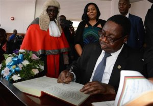 Newly elected Malawian president Peter Mutharika signs the oath book after he was sworn in, at the High Court in Blantyre, Malawi, Saturday May 31, 2014. Malawi's election commission has declared opposition leader  Mutharika to be the winner of an election that was marred by scattered unrest and complaints from the president and others that the vote was rigged. (AP Photo/Thoko Chikondi)