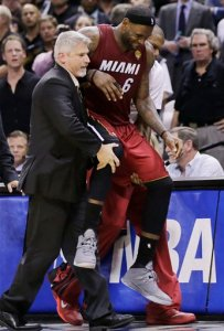 Miami Heat forward LeBron James (6) is carried to the bench after injuring himself against the San Antonio Spurs during the second half in Game 1 of the NBA basketball finals on Thursday, June 5, 2014 in San Antonio. (AP Photo/Eric Gay)