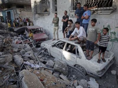 Palestinians look at a destroyed house where five members of the Ghannam family were killed in an Israeli missile strike early Friday morning in the Rafah refugee camp in the southern Gaza Strip (Khalil Hamra/AP)