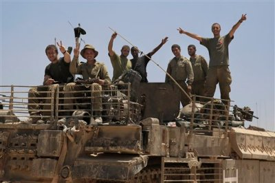 Israeli soldiers give the victory sign on the top of armored vehicle near the Israel Gaza border, Tuesday, July 29, 2014. Israel unleashed its heaviest bombardment in a 3-week-old war against Hamas on Tuesday, striking symbols of the militant group's control in Gaza and firing tank shells that Palestinian officials said shut down the strip's only power plant. (AP Photo/Tsafrir Abayov)