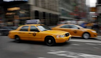 In this Thursday, Feb. 27, 2014 file photo, New York City taxis drive through New York's Times Square. The car-hailing service Uber is taking on New York City's taxis, temporarily dropping some of its prices by 20 percent starting Monday, July 7, 2014. (AP Photo/Richard Drew)