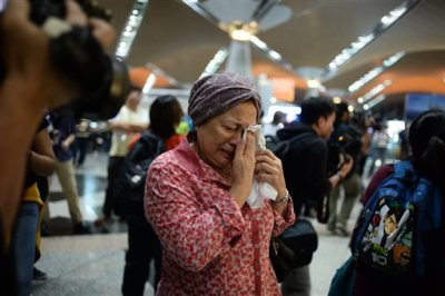 A woman reacts to news regarding a Malaysia Airlines plane that crashed in eastern Ukraine at Kuala Lumpur International Airport in Sepang, Malaysia, Friday, July 18, 2014.  Malaysia Airlines said it lost contact with Flight 17 over Ukrainian airspace Thursday. It was flying from Amsterdam to Kuala Lumpur, Malaysia. (AP Photo/Joshua Paul)
