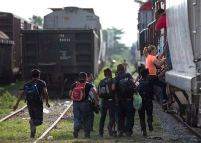 In this Saturday, July 12, 2014 file photo, immigrants run to jump on a train during their journey toward the U.S.-Mexico border, in Ixtepec, Mexico. Many of the immigrants recently flooding the nation's southern border say they're fleeing violent gangs in Central America. These gangs were a byproduct of U.S. immigration and Cold War policies, specifically growing from the increase in deportations in the 1990s. With weak dysfunctional governments at home, U.S. street gang culture easily took hold and flourished in these countries. (AP Photo/Eduardo Verdugo)