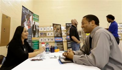 In this photo taken Wednesday, July 16, 2014, job seeker U.S. Air Force veteran Jesse Jefferson, Jr., right, talks to Arianna Alexander, of the Pompano Beach Veterans Center, at a Hiring Fair For Veterans in Fort Lauderdale, Fla. Florida led the nation in job growth in June, a sharp turnaround from the previous month. (AP Photo/Alan Diaz)