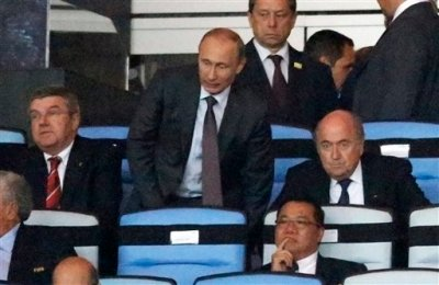 Russian President Vladimir Putin, standing, is flanked by IOC president Thomas Bach, left, and FIFA President Sepp Blatter while watching the World Cup final soccer match between Germany and Argentina at the Maracana Stadium in Rio de Janeiro, Brazil, Sunday, July 13, 2014. (AP Photo/Frank Augstein)