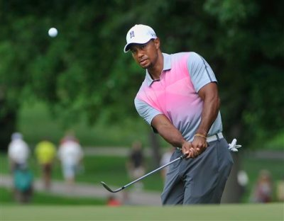 Tiger Woods watches his chip to the fourth hole, during the first round of the Bridgestone Invitational golf tournament, Thursday, July 31, 2014, in Akron, Ohio. (AP Photo/Phil Long)