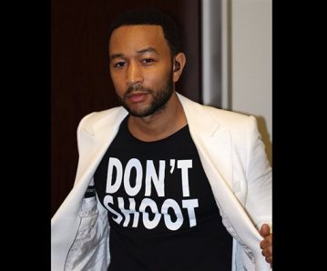 "This Aug. 20, 2014 photo released by singer John Legend shows Legend wearing a T-Shirt that says ""Don't Shoot,"" in reference to the Aug. 9 shooting of Michael Brown in Ferguson, Mo., at the Hollywood Bowl in Los Angeles. Legend performed Marvin Gaye's What's Going on with the Los Angeles Philharmonic. (AP Photo/Ron Stephens II)"