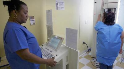 In this photo taken on Thursday, May. 6, 2010, a mammographer performs an advanced imaging screening that promotes early detection of breast cancer. (AP Photo/Damian Dovarganes)