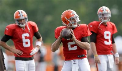 Cleveland Browns quarterback Johnny Manziel (2) gets ready to throw as quarterbacks Brian Hoyer (6) and Connor Shaw (9) watch during practice at the NFL football team's training camp Tuesday, Aug. 5, 2014, in Berea, Ohio. (AP Photo/Tony Dejak)