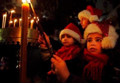Palestinian Christian children wear festive hats as they light candles inside the Church of Nativity, believed by many to be the birthplace of Jesus Christ, during Christmas celebrations in the West Bank town of Bethlehem, Wednesday, Dec. 24, 2008. Tourists from all over the world flocked to Jesus' traditional birthplace on Wednesday to celebrate Christmas Eve. (AP Photo/Tara Todras-Whitehill)