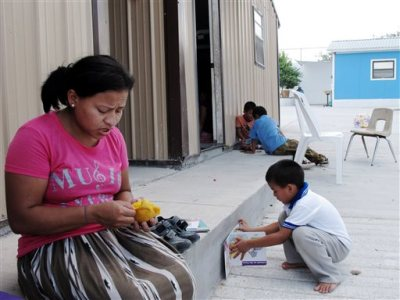 This Aug. 4, 2014 photo shows Eneyda Alvarez of Honduras peeling a mango while her son Antony plays at the Senda de Vida migrant shelter in Reynosa, Mexico. Alvarez hopes to join the thousands of families _ mothers or fathers with young children _ who have crossed the Rio Grande into the U.S. United States. (AP Photo/Christopher Sherman)