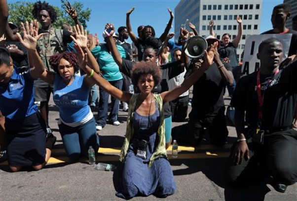 Protestors drop to their knees and put their arms in the air during a rally for Michael Brown Jr., who was shot and killed by a Ferguson police officer last Saturday, Tuesday, Aug. 12, 2014, in Clayton, Mo. (AP Photo/St. Louis Post-Dispatch, Laurie Skrivan)