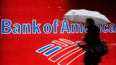 In this Dec. 7, 2011 photo, a woman passes a Bank of America office branch, in New York. Bank of America said Jan. 19, 2012, it made $2 billion in the last three months of 2011 from selling its stake in a Chinese bank and selling debt. That offset losses and higher legal expenses in its mortgage business. (AP Photo/Mark Lennihan)
