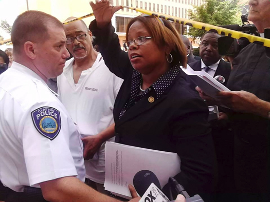 Police officer blocks State Representative Jamilah Nasheed from entering a government building Aug. 21, 2014. She was eventually given entrance after shouts and coalition. (Courtesy of The Final Call)