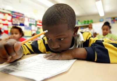 A student reads at a school in New Jersey. One in four black students were suspended in 2009-10, compared to one in fourteen white students. (AP Photo/Jose F. Moreno.)