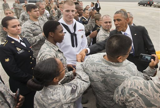 President Barack Obama greets members of the military upon his arrival on Air Force One at MacDill Air Force Base, Tuesday, Sept. 16, 2014. Obama will spend the night in Tampa and tomorrow morning he will receive a briefing at US Central Command about the ongoing military campaigns in Iraq and Syria. (AP Photo/Pablo Martinez Monsivais)