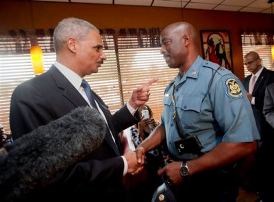 In this Aug. 20, 2014 file photo, Attorney General Eric Holder talks with Capt. Ron Johnson of the Missouri State Highway Patrol at Drake's Place Restaurant in Florrissant, Mo.  The Justice Department plans to open a wide-ranging investigation into the practices of the Ferguson, Missouri, Police Department following the shooting last month of an unarmed black 18-year-old by a white police officer in the St. Louis suburb, a person briefed on the matter said Wednesday, Sept. 3, 2014.  (AP Photo/Pablo Martinez Monsivais, File-Pool)