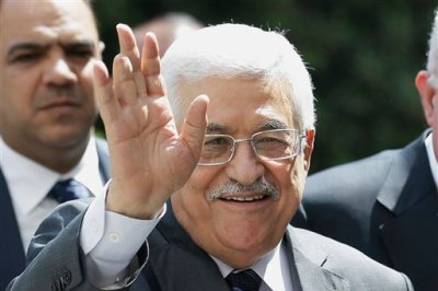 Palestinian President Mahmoud Abbas waves to photographers as he arrives to attend an Arab foreign minister meeting at the Arab League headquarters in Cairo, Egypt, Sunday, Sept. 7, 2014. Abbas threatened to dissolve a new unity government if the Hamas militant group does not yield power in the Gaza Strip. (AP Photo/Hassan Ammar)