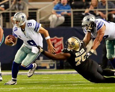 """Dallas Cowboys quarterback Tony Romo (9) escapes from New Orleans Saints defensive end Tyrunn Walker (75) during the second half of an NFL football game Sunday, Sept. 28, 2014, in Arlington, Texas. NBC's """"Sunday Night Football"""" charges $627,300 for a 30-second advertisement, more than any other program in prime-time broadcast television, according to a survey by Advertising Age. On its heels is CBS' new Thursday night football telecast, being shown this fall for the first time, at $483,333. (AP Photo/The Waco Tribune-Herald, Jose Yau)"""