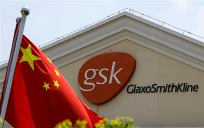 In this July 24, 2013 file photo, a Chinese flag is hoisted in front of a GlaxoSmithKline building in Shanghai, China. Drug maker GlaxoSmithKline was fined $492 million on Friday, Sept. 19, 2014 for bribing doctors in China in the biggest such penalty ever imposed by a Chinese court. The court sentenced the company's former China manager, Briton Mark Reilly, and four Chinese co-defendants to prison but postponed the sentences for two to four years, suggesting they may never be served. The court said it granted leniency because the defendants confessed. (AP Photo/Eugene Hoshiko, File)