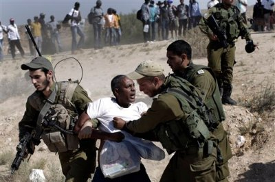 In this Friday, June 27, 2014 file photo, African migrants clash with Israeli soldiers after they left Holot detention center in southern Israel and walked towards the Border with Egypt near the southern Israeli Kibbutz of Nitzana. In a report issued Tuesday, Sept. 9, 2014, Human Rights Watch says Israeli authorities have coerced almost 7,000 Eritrean and Sudanese to return to their homes, where they may face serious abuse. (AP Photo/Tsafrir Abayov, File)