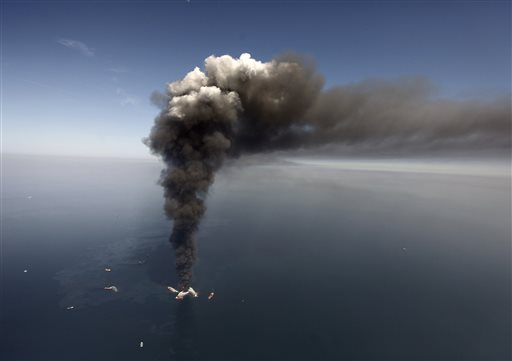 In this Wednesday, April 21, 2010 file photo, oil can be seen in the Gulf of Mexico, more than 50 miles southeast of Venice on Louisiana's tip, as a large plume of smoke rises from fires on BP's Deepwater Horizon offshore oil rig. An April 20, 2010 explosion at the offshore platform killed 11 men, and the subsequent leak released an estimated 172 million gallons of petroleum into the gulf. U.S. District Judge Carl Barbier ruled Thursday, Sept. 4, 2014, in New Orleans, La., that BP acted recklessly and bears most of the responsibility for the oil spill. The ruling exposes BP to about $18 million in civil fines under the Clean Water Act. (AP Photo/Gerald Herbert, File)