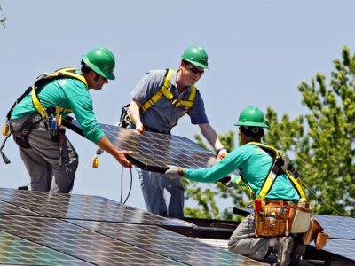 In this June 18, 2010, file photo, U.S. Senator Michael Bennet, D-Colo., center, helps as Solar City employees Jarret Esposito, left, and Jake Torwatzky, right, install a solar panel on a home in south Denver. The solar panel installer SolarCity said Wednesday, Jan. 15, 2014, it will launch an investment platform that will allow individuals and others to invest in rooftop solar systems directly with SolarCity. (AP Photo/Ed Andrieski, File)