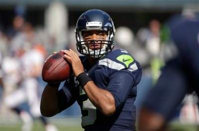 In this  Sunday, Sept. 21, 2014 file photo, Seattle Seahawks quarterback Russell Wilson passes during warmups before an NFL football game against the Denver Broncos in Seattle. Seattle Seahawks quarterback Russell Wilson is speaking out about domestic violence and about being a bully as a child in a column for Derek Jeter's new website. Wilson was announced as a senior editor for The Players' Tribune on Thursday morning, Oct. 2, 2014. (AP Photo/Elaine Thompson, File)