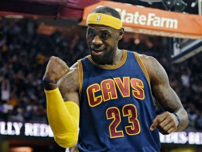 Cleveland Cavaliers' LeBron James gestures to the crowd in the first quarter of an NBA basketball game against the New York Knicks Thursday, Oct. 30, 2014, in Cleveland. (AP Photo/Tony Dejak)