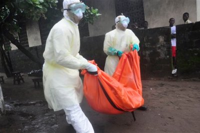 Health workers in protective gear carry the body of a woman suspected to have died from Ebola virus, from a house in New Kru Town at the outskirt of Monrovia, Liberia, Wednesday, Oct. 8, 2014. Liberia has been among the hardest hit nations at the centre of the long outbreak, which has killed more than 3,000 people, as of Friday, there had been 3,834 confirmed Ebola cases and 2,069 deaths in Liberia, according to the World Health Organization. Forty-four percent of the Ebola cases were reported in the past three weeks, a signal that the infectious disease is spreading. (AP Photo/Abbas Dulleh)