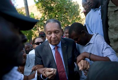 "In this Feb. 8, 2011 file photo, former Haitian dictator Jean-Claude ""Baby Doc"" Duvalier's supporters help him negotiate an uneven path during a visit to his mother's hometown and grave site in Leogane, Haiti. Duvalier, the self-designated ""president-for-life"" who died Oct. 4, 2014, from an apparent heart attack, will not get a formal state funeral, but have a ""simple, private,""funeral arranged by friends and family in Haiti, attorney Reynolds Georges said in an interview. (AP Photo/Ramon Espinosa, File)"