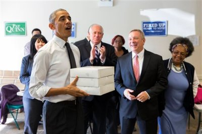 Gov. Pat Quinn, D-Ill., center, and Sen. Dick Durbin, D-Ill., second from right, watch as President Barack Obama delivers doughnuts and pastries to Democratic campaign volunteers on Monday, Oct. 20, 2014, in Chicago. Obama is in Chicago campaigning for Gov. Pat Quinn, D-Ill. (AP Photo/Evan Vucci)
