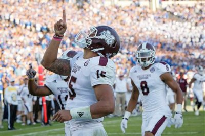 In this Oct. 25, 2014, file photo, Mississippi State quarterback Dak Prescott celebrates after running for a touchdown during the second half of an NCAA college football game against Kentucky at Commonwealth Stadium in Lexington, Ky. The first of seven top-25 rankings done by a 12-member selection committee was released Tuesday, Oct. 28, 2014. Mississippi State, Florida State, Auburn, Mississippi are the top four teams in the first College Football Playoff rankings. (AP Photo/David Stephenson, File)