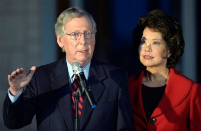 """This Oct. 2, 2014, file photo shows  Senate Minority Leader Mitch McConnell of Ky., left, joined by his wife Elaine Chao as he speaks to media at Donamire Farm in Lexington. In a debate with his Democratic re-election opponent, McConnell said that Obama's health care law must be pulled up """"root and branch."""" But he hastened to add that the state could somehow still keep its insurance marketplace, which owes its existence to Obama's law. (AP Photo/Timothy D. Easley, File)"""