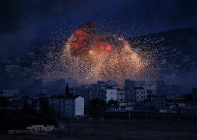 In this Monday, Oct. 20, 2014 file photo, thick smoke and flames from an airstrike by the U.S.-led coalition rise in Kobani, Syria, as seen from a hilltop on the outskirts of Suruc, at the Turkey-Syria border. Al-Qaida is using U.S. airstrikes in Syria as a reason to extend olive branches to the renegade Islamic State group, saying the two should stop feuding and join forces to attack Western targets,  a reunification that intelligence analysts say would allow al-Qaida to capitalize on the younger group's ruthless advance across the region. (AP Photo, Lefteris Pitarakis, File)