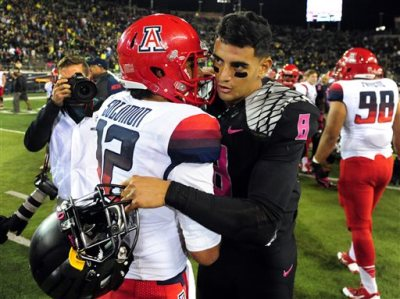 Arizona quarterback Anu Solomon (12) shakes hands with Oregon Ducks quarterback Marcus Mariota (8) after the NCAA college football game at Autzen Stadium on Thursday, Oct. 2, 2014, in Eugene, Ore. Arizona won the game 31-24.(AP Photo/Steve Dykes)