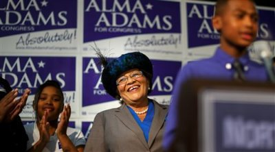 Democrat Alma Adams smiles as her grandson lauds her before she gives her victory speech after winning North Carolina's 12th Congressional District at the Greensboro Coliseum in Greensboro, N.C., on Tuesday, Nov. 4, 2014. (AP Photo/News & Record, Jerry Wolford)