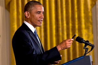"""President Barack Obama holds up a pen that he used to take notes during a reporter's multi-part question during a news conference in the East Room of the White House, Wednesday, Nov. 5, 2014, in Washington. Obama is telling Americans who voted for change: """"I hear you."""" The President said the Republican victories Tuesday in the midterm elections are a sign they want Washington """"to get the job done."""" (AP Photo/Jacquelyn Martin)"""